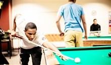 Student playing pool in the game room