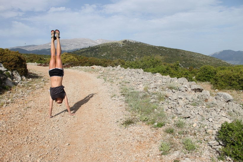 Student doing a handstand on a trail