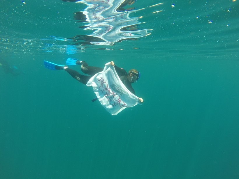 Student snorkeling with a Roanoke College banner