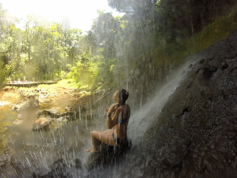 Student sitting under a small waterfall