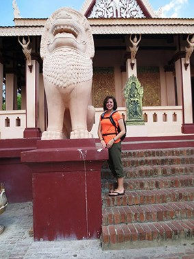 Student posing by a statue of a lion in Cambodia