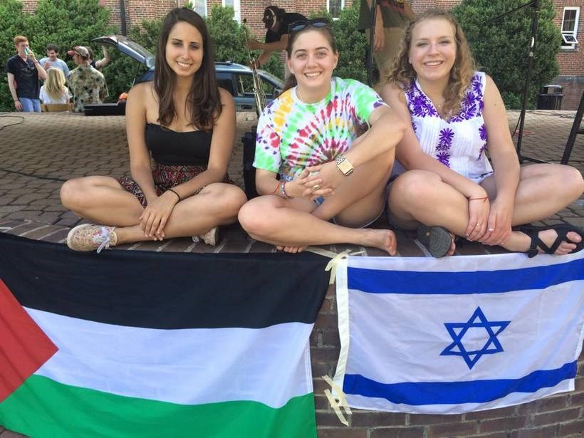 Students posing by flags from different countries