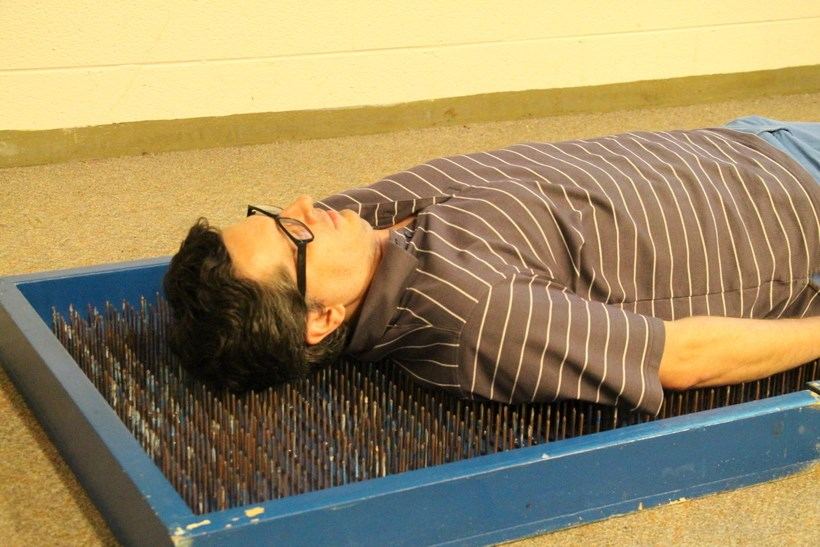 Professor laying on a bed of nails