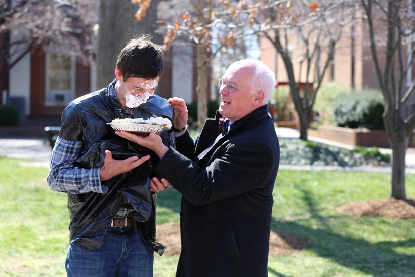 President Maxey throwing a pie in another student's face