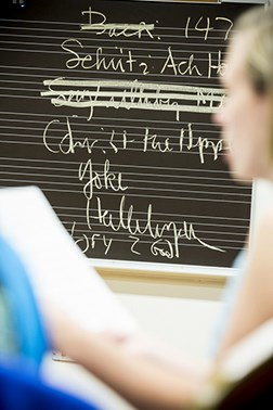 Students in class by a chalkboard with names of songs on it