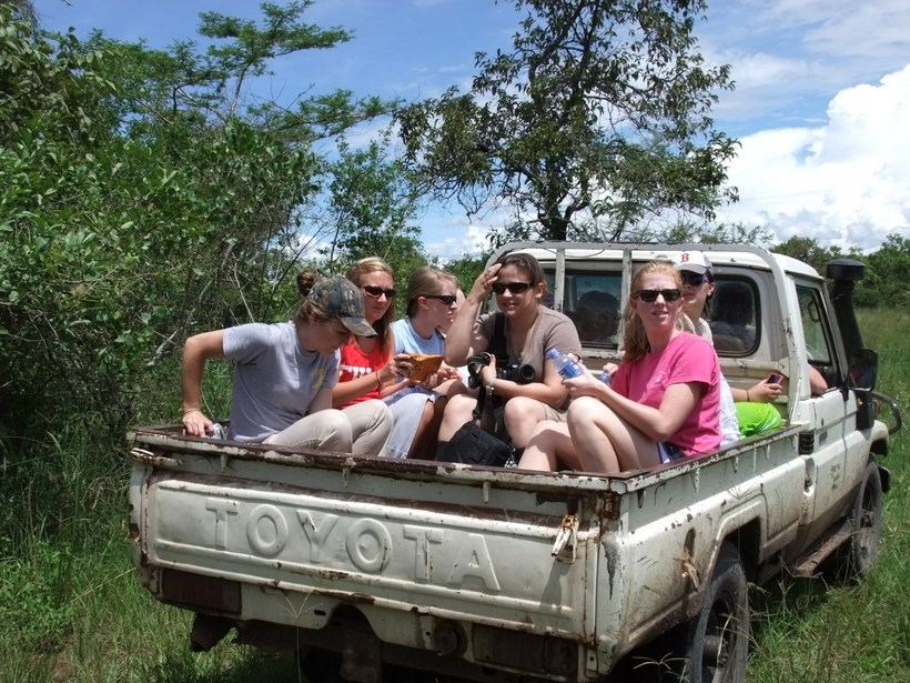 Students sitting in the bed of a pickup truck
