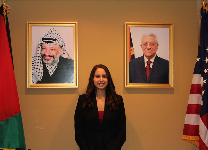 Student posing by portraits in a government building