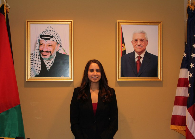 Student posing near portraits in a government building