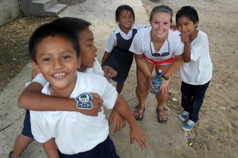 Student with children in Belize