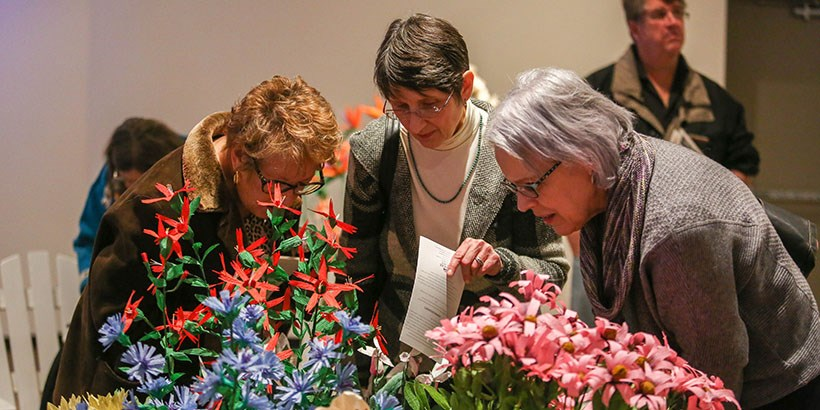 three women look up close at the blue, pink and red flowers