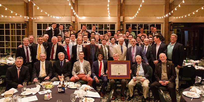 Pi Lambda Phi members and alumni members holding the recharter document at their recharter celebration
