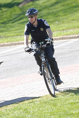 An officer from Campus Safety riding his bike around campus