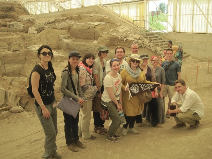 Roanoke students and their professor hold up a Roanoke flag infront of a archeological dig