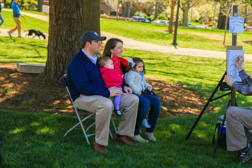 Alumni and their two daughters get a caricature drawing done on the Back Quad.
