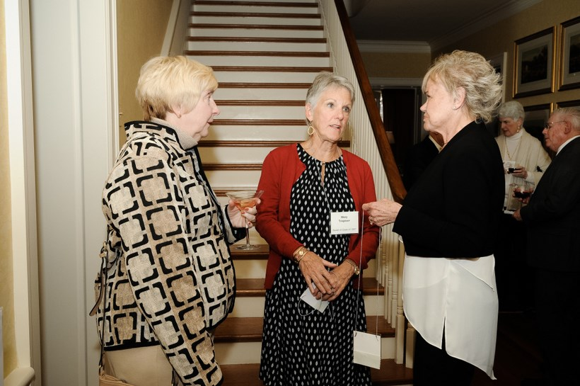 Three alumni chatting in the Foyer of the Maxey's house.