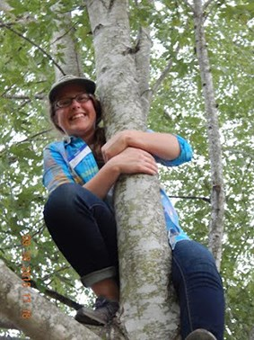 Student takes a break from climbing a tree to smile for a picture