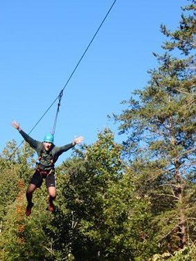 Student cruising on a zip-line