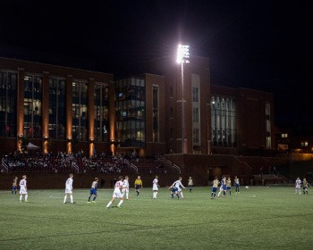 Men's soccer team playing outside at night under the lights