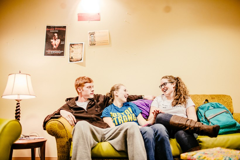 Students hanging out and talking on a couch