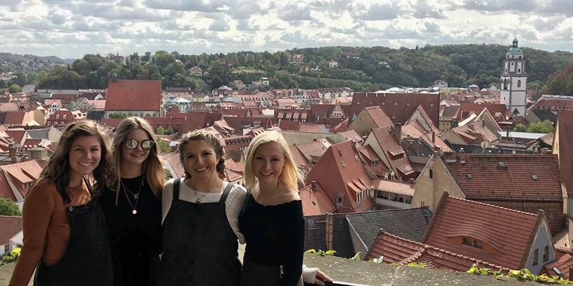 Students standing at an overlook of a German city