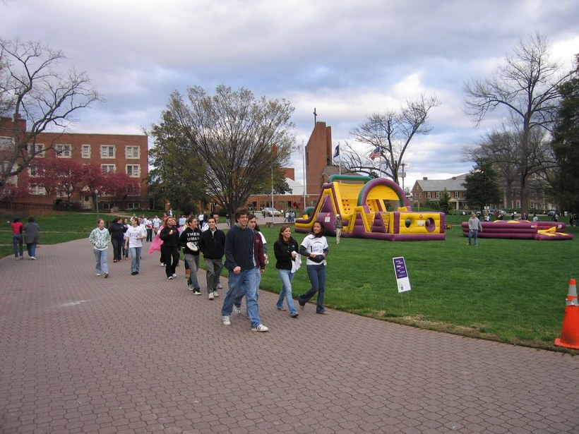 Students walking past a bouncy house on the quad