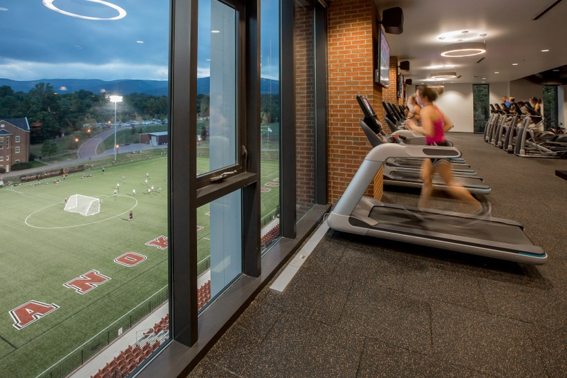Students in the workout center in the Cregger Center by large windows