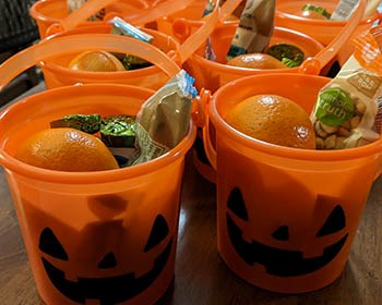 Orange pumpkins with jack-o-lantern faces filled with fruit, nuts, and candy