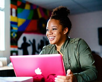A student smiling and sitting at her laptop
