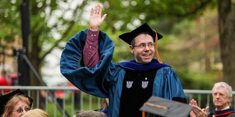 Chris Lassiter standing and raising a hand at commencement