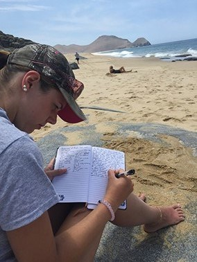Student journaling at the beach