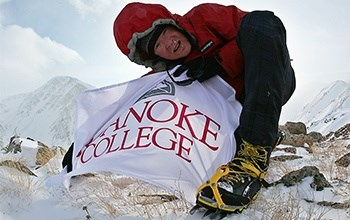 Sean Burch on top of a snowy mountain holding a Roanoke College flag