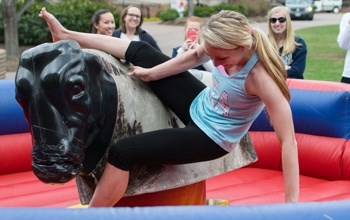 Student riding and falling off of a mechanical bull