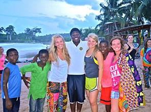 Students posing with community members in Africa
