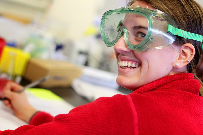 Student smiling while writing notes for a lab