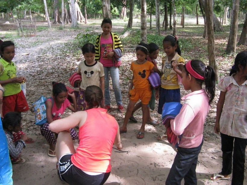 Student with a group of children in Cambodia