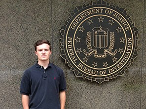 Student standing next to the FBI seal on a building