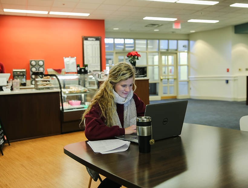 Student working by the cafe in the library