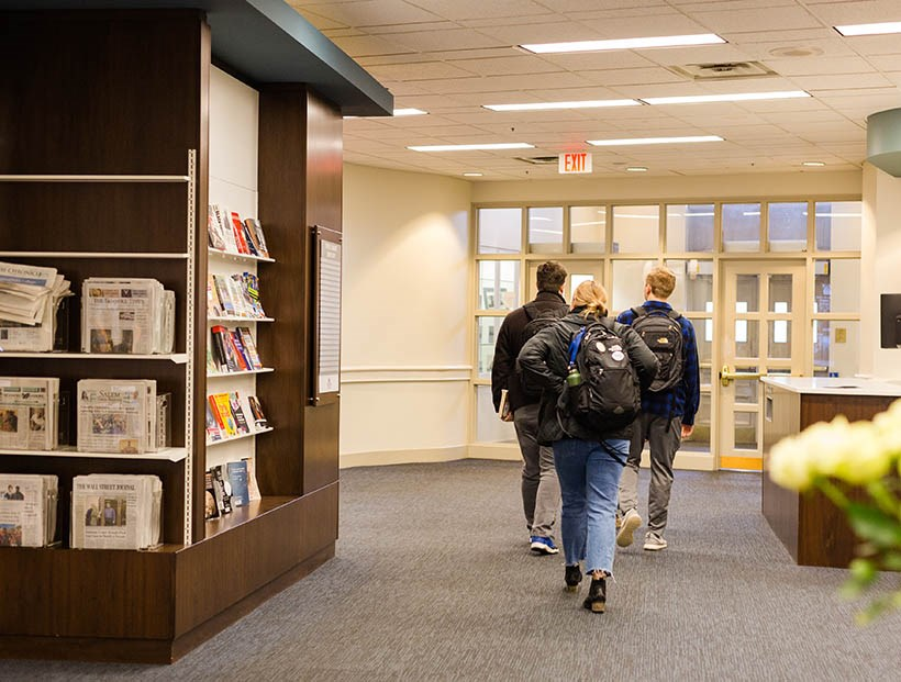 Students walking next to Bookshelves in Fintel Library