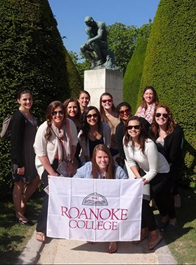 Students posing in front of a sculpture with a roanoke college banner