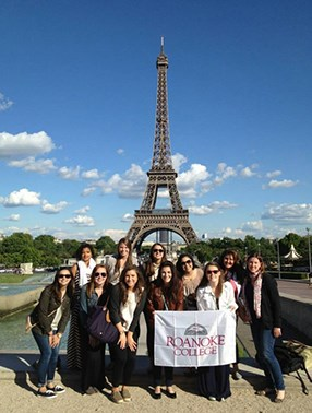 Group of students at the Eiffel tower with a Roanoke College banner