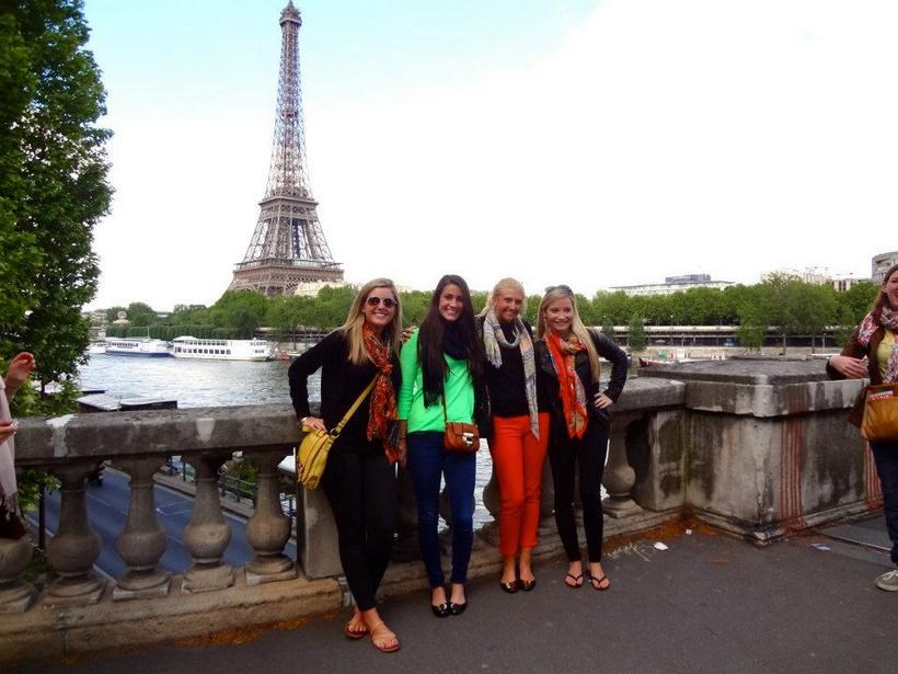 Photo of students on a bridge over the river Seine with the Eiffel tower in the background