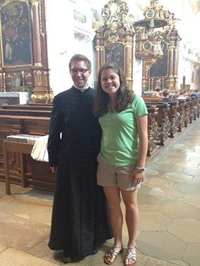 Student standing with a pastor in a German church
