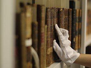 Gloved hand touching old books