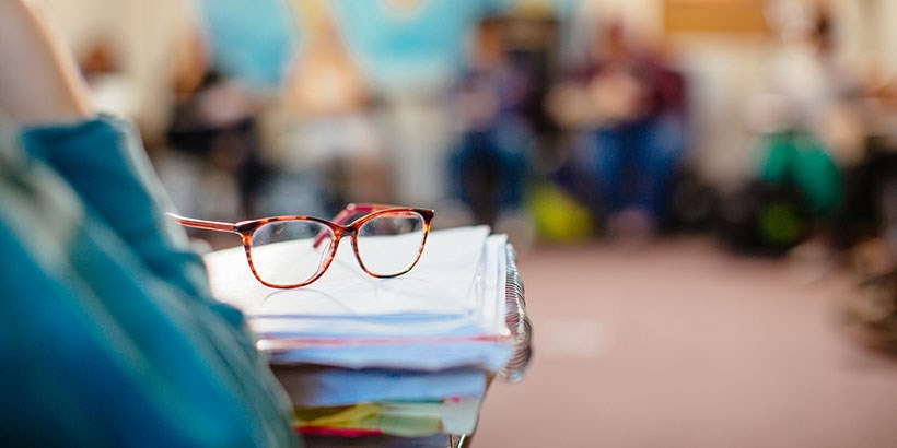 Closeup on a pair of glasses on top of a stack of open notebooks