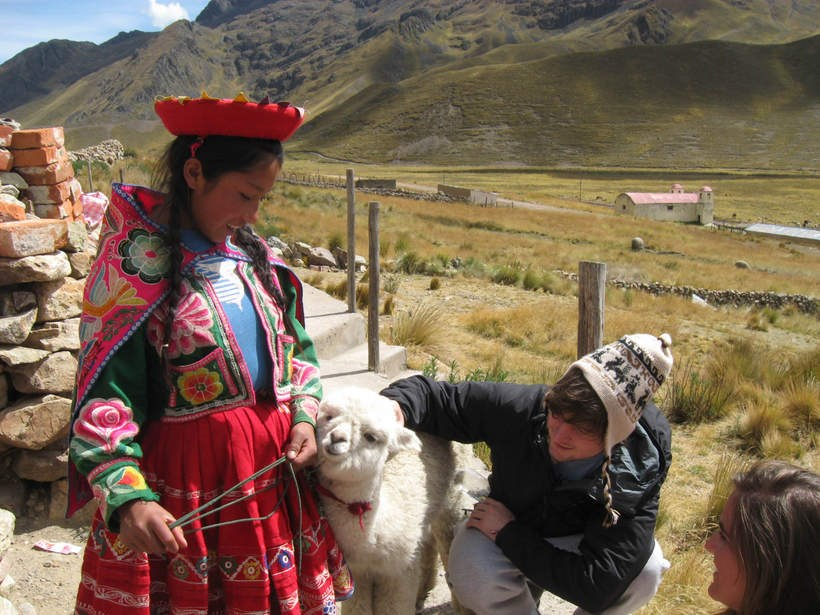 Students petting a lamb in a Latin American country
