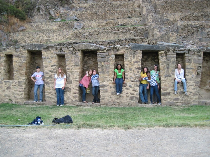 Students posing for pictures inside ruins in a Latin American country