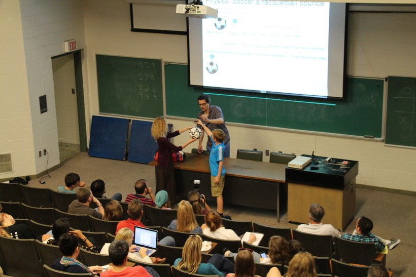 Students trying a magic trick with a professor