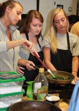 Students cooking greens in a pan