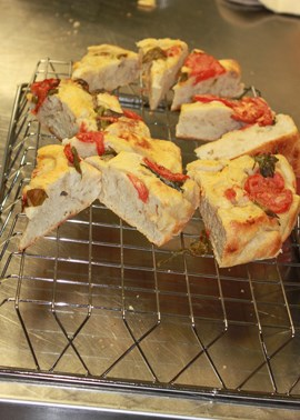 Slices of bread with tomatoes and basil on a cooling rack