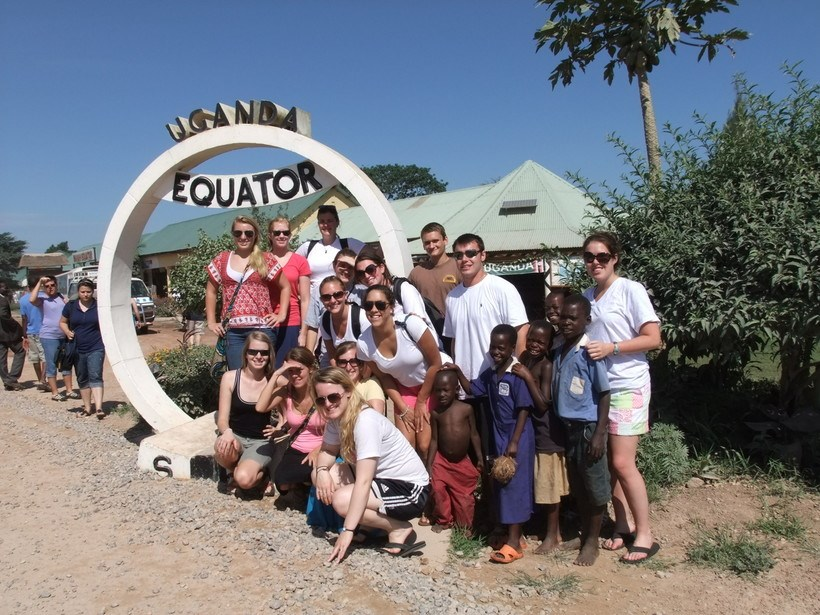 Students posing by the sign signifying where the equator is